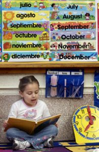 A student reads a book in Spanish in a bilingual classroom