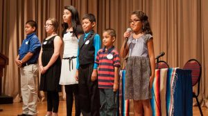 Several bilingual students speaking at an event